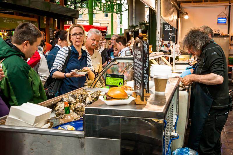Auf dem Borough Market geht es am Wochenende recht tumultartig zu. Auch für Austern muss man hier Schlange stehen. Wer auf Burger de luxe oder Burritos steht, muss länger warten / © FrontRowSociety.net, Foto: Georg Berg