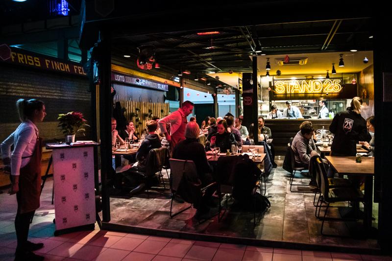 Wie eine warme, leuchtende Insel der Glückseligkeit. Wenn die Marktstände schon längst geschlossen sind, wird es erst richtig munter im Stand 25. Wer für Abends einen Tisch reserviert, wird an der Eingangspforte der ehrwürdigen Markthalle an der Stand Utca abgeholt / © FrontRowSociety.net, Foto: Georg Berg