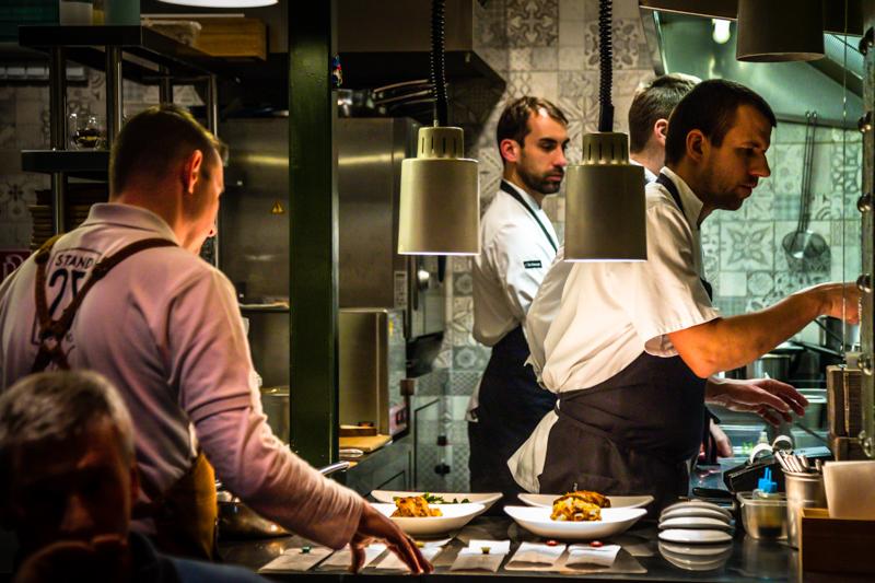 Bestens organisiert auf engstem Raum: László Papdi mit Kollegen in der offenen Küche des Stand 25 im Hold Street Market / © FrontRowSociety.net, Foto: Georg Berg