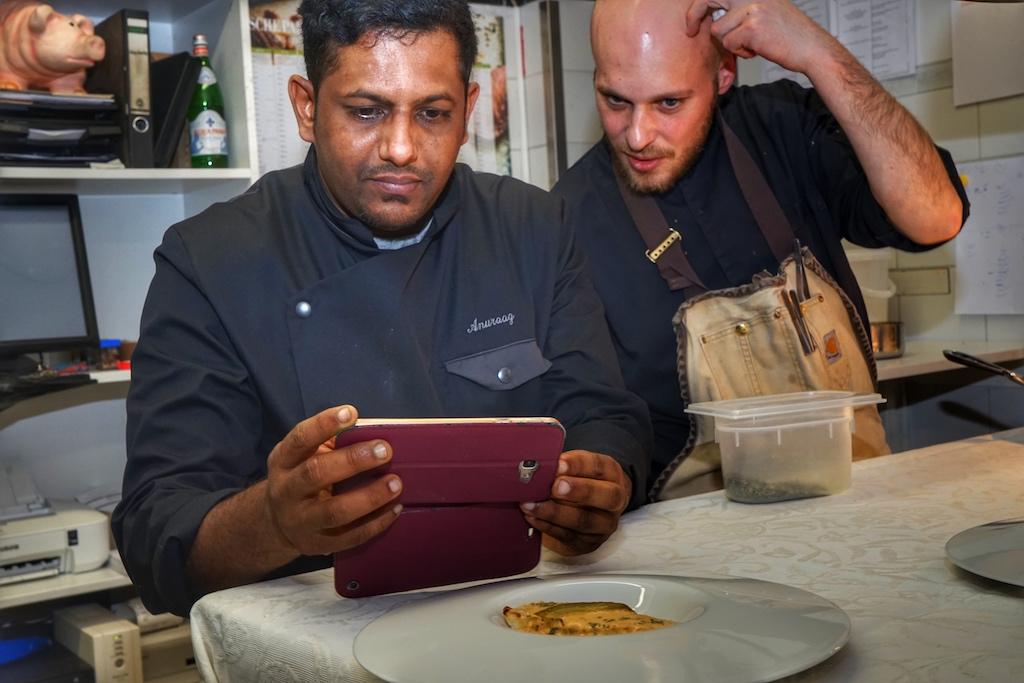 Auch Anuraag Ramkalawon (li.) hält seine Kreationen digitale fest. Simon Stirnal (re.) - kulinarischer Gastgeber des Rheingau Gourmet & Wein Festival - mit prüfendem Blick