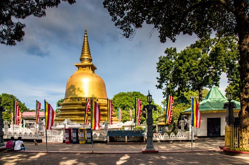 Die typischen Buddhismus-Fahnen wehen um die Pagode des Goldenen Tempels von Dambulla / © FrontRowSociety.net, Foto: Georg Berg