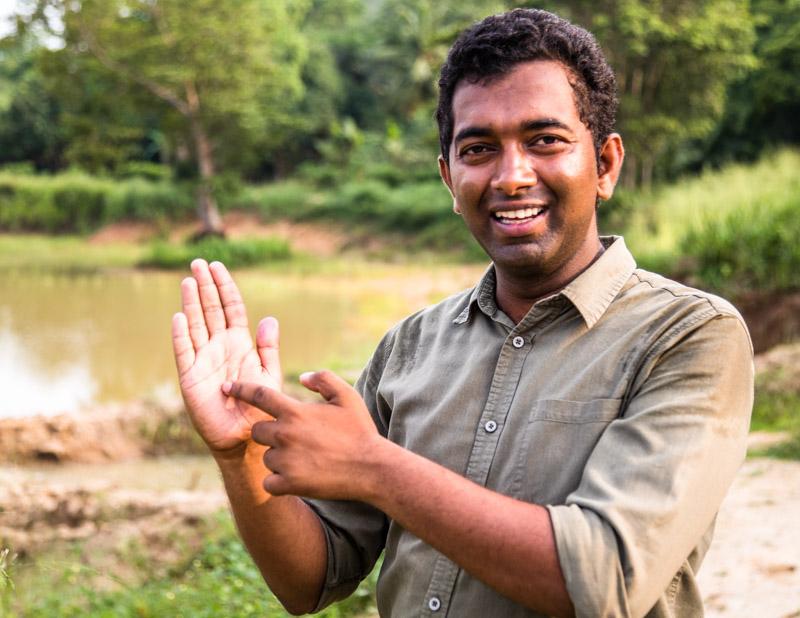 Ishanda zeigt auf seiner Sri Lanka darstellenden Handfläche, wo wir uns befinden. Er hält als vom Hotel angestellter Umweltschützer auch den Kontakt zur Dorfgemeinschaft / © FrontRowSociety.net, Foto: Georg Berg
