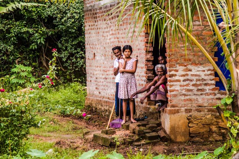 """""""Ayubowan"""" (mögest du lang leben) Eine Bauernfamilie ruft uns die landestypische Begrüßung zu / © FrontRowSociety.net, Foto: Georg Berg"""