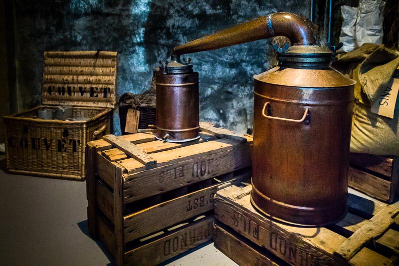 Im Absinth Museum in Motiers ist diese Destillieranlage hinter einer knarzenden Zimmertür versteckt und so wird sehr anschaulich die Zeit der Schwarzbrennerei im Val de Travers erlebbar. Bei der Herstellung von Absinth werden gut getrockneter Wermut, Anis, Fenchel und weitere Kräuter in Neutralalkohol eingeweicht und anschließend destilliert. Der Alkoholgehalt des historischen Absinth lag zwischen 48 und 78 Volumenprozent Alkohol / © FrontRowSociety.net, Foto: Georg Berg