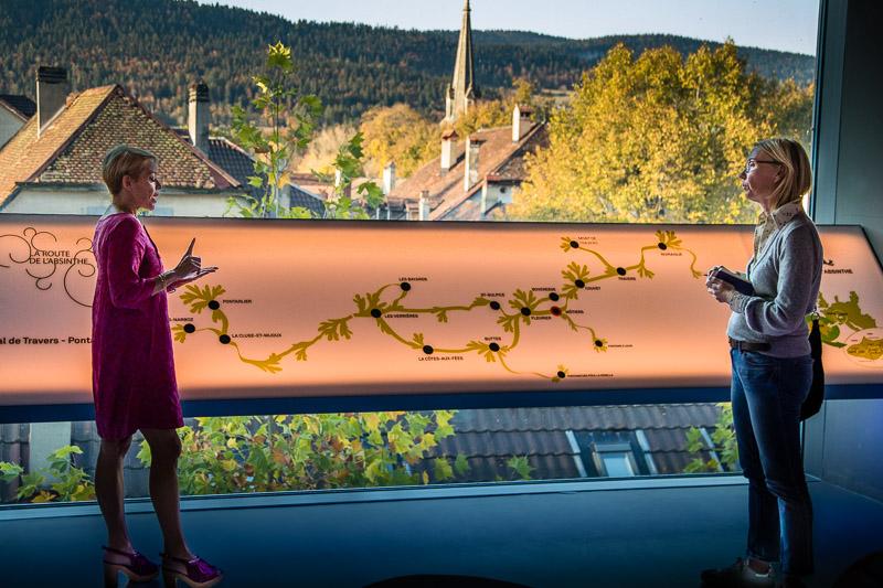Im Gespräch mit Montse Lucas. Die Spanierin führt sehr kompetent durch die vielseitige Ausstellung im Maison de Absinthe von Motiers. Hier stehen wir vor einer Tafel, die die Route des Absinth zeigt. Eine Wanderstrecke von nur 48 Kilometern verbindet das französische Pontarlier mit dem schweizerischen Noiraigue. Auf der Route liegen zahlreiche Destillerien, Brasserien, Gasthöfe, Museen, Burgen, Hotels und Restaurants, die sich dem Thema Absinth annehmen oder seine Geschichte mitprägten / © FrontRowSociety.net, Foto: Georg Berg