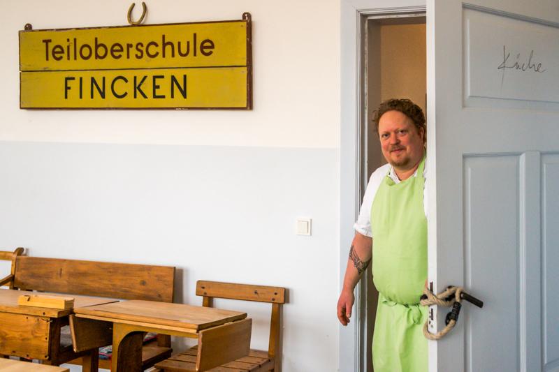 """Der Chef in seinem """"Klassenzimmer"""". Seit 2015 kocht und serviert Gunnar Müller in den ehemaligen Klassenräumen der Teiloberschule Fincken / © FrontRowSociety.net, Foto: Georg Berg"""