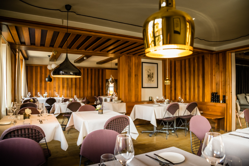 Das Restaurant im Hotel Krone mit 30 Sitzgelegenheiten. Viele von ihnen sind der Eames Wire Chair DKW von 1951. Über den Tischen schweben Klassiker des Lichtdesigns. Im Vordergrund die Leuchte Golden Bell von Artek / © FrontRowSociety.net, Foto: Georg Berg