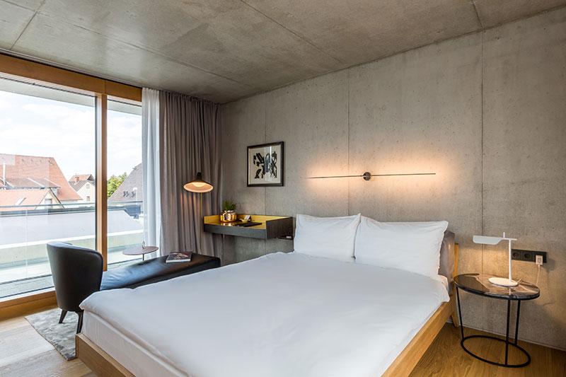Zimmer im Neubau des Hotels Krone in Weil am Rhein mit viel Sichtbeton. In die gegenüberliegende Lehmwand wurden sogar Kräuter eingearbeitet . Sie sorgt so für ein angenehmes Raumklima. Dazu harmonieren Stoffe wie Samt und Leder. Die Möbel sehr pointiert gesetzt. Das Bett Mellow von Zeitraum, statt Bettsims schließt es an der Kopfseite mit hinreißend schlichten Lederkissen ab. Die Wandleuchte ist von Sastellan & Smith und die Spiegel in den Bädern von Gubi. In jedem Raum stehen Vitra Stühle und Tische / © Hotel Krone