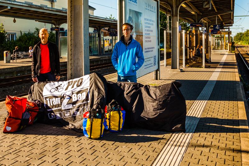 Chefreporter Georg Berg mit Sohn Julius; auf dem Bahnsteig das Gepäck bestehend aus Satteltaschen und verpackten Fahrrädern / © FrontRowSociety.net, Foto: Georg Berg