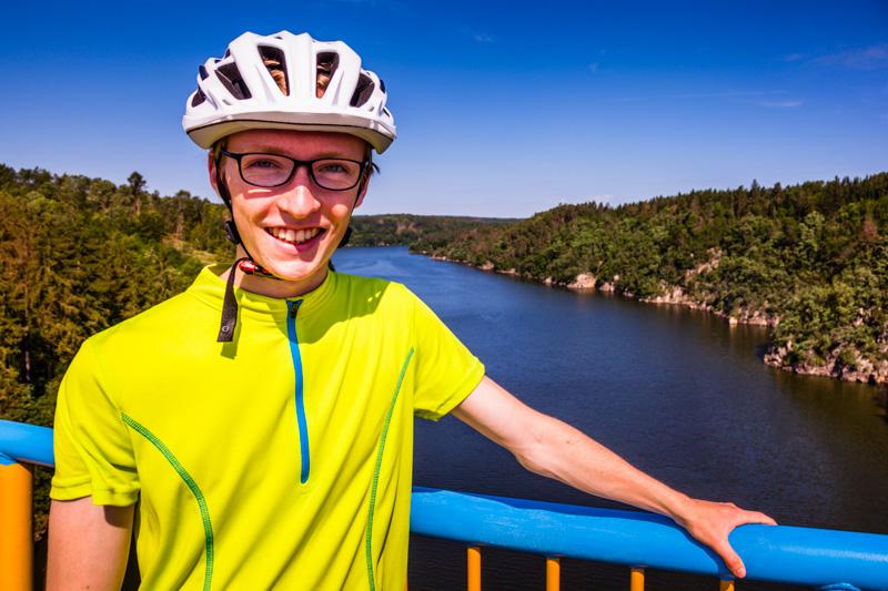 Julius Berg auf einer Moldaubrücke. Das Ufer ist über weite Strecken im ursprünglichen Zustand und die meisten Radwege führen über das hügelige Hinterland / © FrontRowSociety.net, Foto: Georg Berg