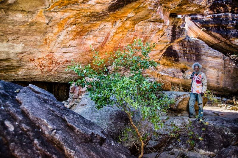 Thommo zeigt auf das Abbild eines Mimi Geistes. Dabei hält er ängstlich einen großen Abstand zu diesem Bild ein. Er ist sich sicher, ein Bild vor sich zu haben, dass nur von den Mimi-Spirits selbst gemalt worden sein kann / © FrontRowSociety.net, Foto: Georg Berg