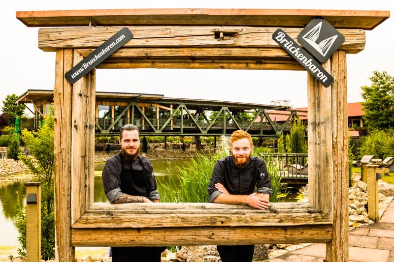 Die beiden Kochtalente Marcel Meining (l.) und Alexander Gläsel (r.) und nur der Brückenbaron sprengt den Rahmen / © FrontRowSociety.net, Foto: Georg Berg
