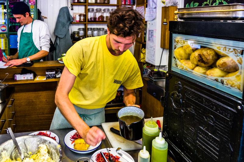 Bei Caspar Plautz entfaltet sich Kreativität auf engstem Raum. Im Ofen garen die Kartoffeln der Sorte Agria, Dominik Klier bereitet die Bestellungen vor. Als Beilage ein Rohkostsalat mit Bio-Gemüsen vom Nachbarstand Trübenecker / © FrontRowSociety.net, Foto: Georg Berg