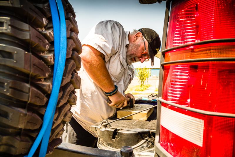 Unterwegs wird der Kofferraum des Landrovers zur Werkbank. Konrad Fobbe fertigt aus einem Stück Gummischlauch ein Ersatzteil / © FrontRowSociety.net, Foto: Georg Berg