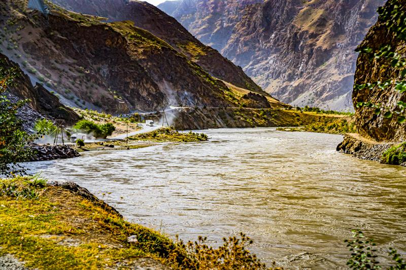 """Der Pansch-River bildet die Grenze zwischen Tadschikistan und Afghanistan. An beiden Ufern des reißenden Flusses verlaufen die uralten Handelsrouten. Links auf tadschikischer Seite verkehren chinesische Laster auf der """"New Silk Road"""". Rechts, auf afghanischer Seite sind nur kleinere Lasttiere und Fahrzeuge zu beobachten / © FrontRowSociety.net, Foto: Georg Berg"""