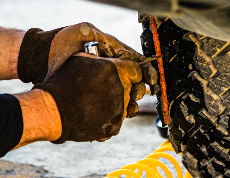 Etwas Kraft ist schon nötig, um den dicken orangen Gummifaden in das vorher gebohrte Loch zu drücken / © FrontRowSociety.net, Foto: Georg Berg