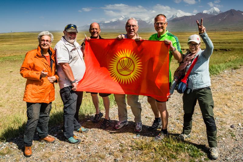 Hinter der kirgisischen Flagge gruppieren sich drei Einzelreisende und ein Ehepaar um Veranstalter Konrad Fobbe (2. v.l.) / © FrontRowSociety.net, Foto: Georg Berg