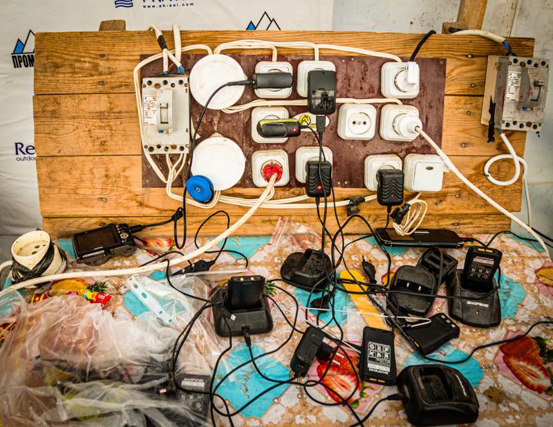 Adapter und Ladegeräte der Expeditions-Funkgeräte scharen sich um den wertvollen Stromanschluss im Basecamp. Wifi bucht man stundenweise für 2 US Dollar / © FrontRowSociety.net, Foto: Georg Berg