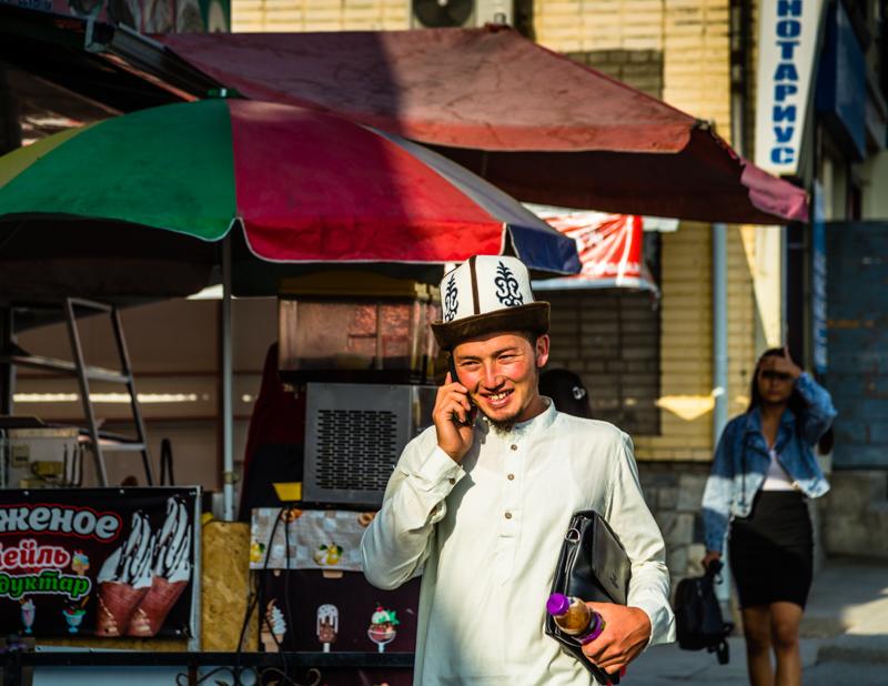 Junger kirgisischer Geschäftsmann unterwegs mit Kalpak, dem traditionell kirgisischen Hut aus weißem Wollfilz / © FrontRowSociety.net, Foto: Georg Berg