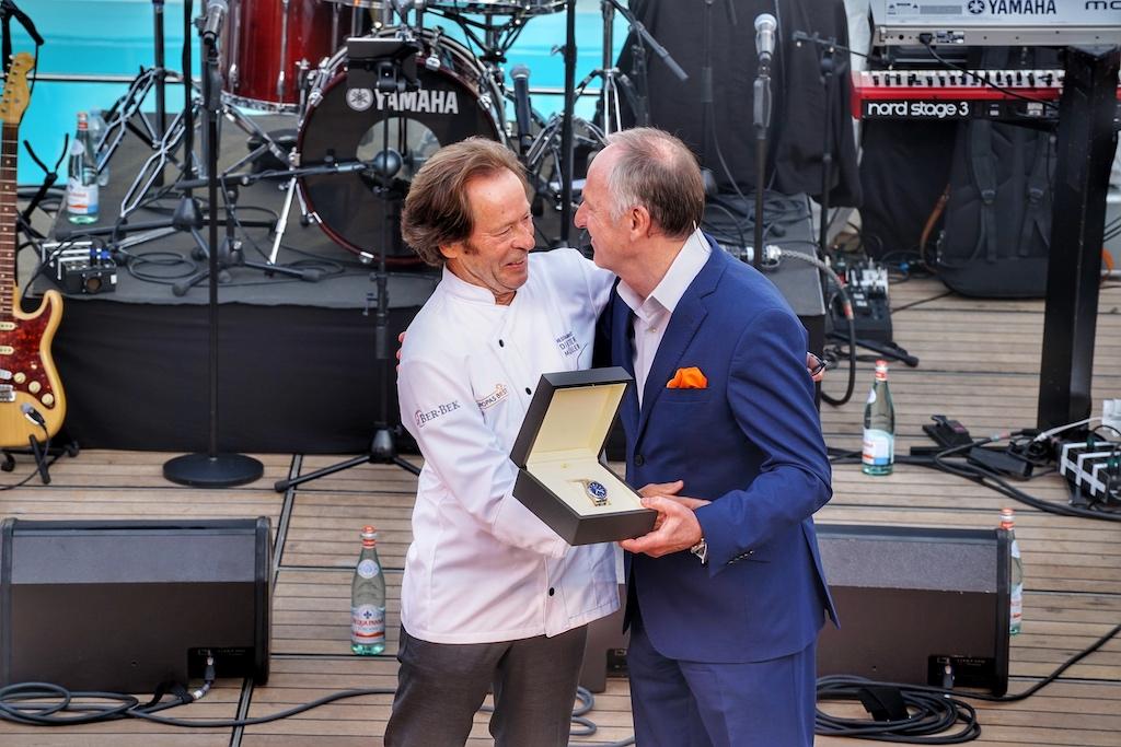 Karl J. Pojer (Vorsitzender der Geschäftsführung von Hapag-Lloyd Cruises) überreicht 3-Sterne Kochlegende Dieter Müller eine besondere Aufmerksamkeit und drückt damit nochmals vor allen Gästen seinen Dank für die vergangenen Jahre aus