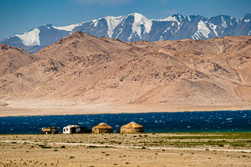 Jurten der kirgisischen Nomaden am tadschikischen Karakul-See, der mit seiner dunklen Farbe einen schönen Kontrast zu den schneebedeckten Gipfeln bildet / © FrontRowSociety.net, Foto: Georg Berg