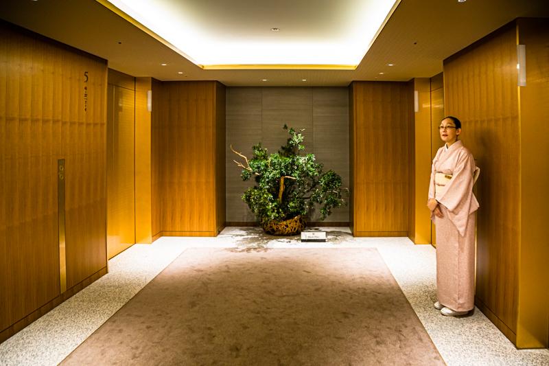 Hüterin der Aufzüge – ein Service im Kimono, den es schon seit den 1960er Jahren gibt. Aus der Lobby geht es in die Höhe. Ab Stockwerk 28 beginnen im Okura Prestige Tower die Gästezimmer / © FrontRowSociety.net, Foto: Georg Berg