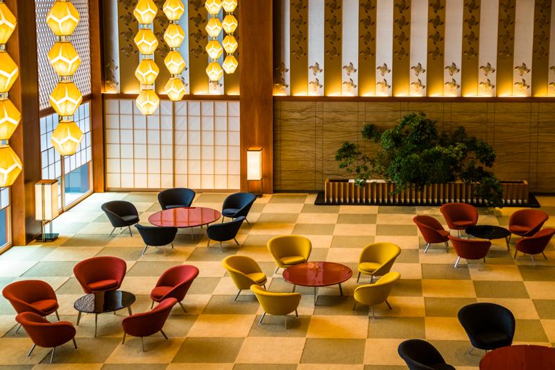 Die Sitzgruppen sind in der Form von Pflaumenblüten arrangiert. Die Möbel sind zwar Repliken, aber die Anordnung rund um die Lacktischchen und auf dem Schachbrettmuster des Teppichs entspricht dem Designentwurf von 1962. Aus Prinzip wird den Gästen auch heute noch in diesem Bereich nichts serviert / © FrontRowSociety.net, Foto: Georg Berg