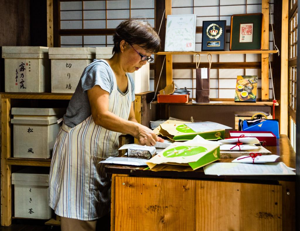 Japaner sind Meister der Verpackung. Frau Uchino schlägt den Tee, den man nur vor Ort in kleinen Mengen erwerben kann, in schöne Umschläge / © FrontRowSociety.net, Foto: Georg Berg