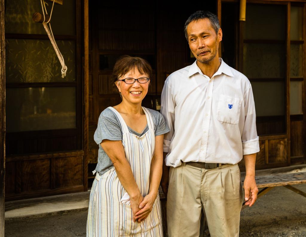 Das Ehepaar Uchino vor ihrer Farm. Der Sohn der Teebauern ist 25 Jahre alt und studiert. Die Eltern hoffen auf den Fortbestand des Familienunternehmens. Doch die Entscheidung hierüber liegt beim Sohn. Noch helfen seine Großeltern helfen bei der Teeverarbeitung mit / © FrontRowSociety.net, Foto: Georg Berg