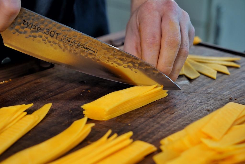 Die Dünnen an der Aufschnittmaschine geschnittenen Kürbisscheiben werden geometrisch in Form einer Raute getrimmt / © Redaktion FrontRowSociety.net