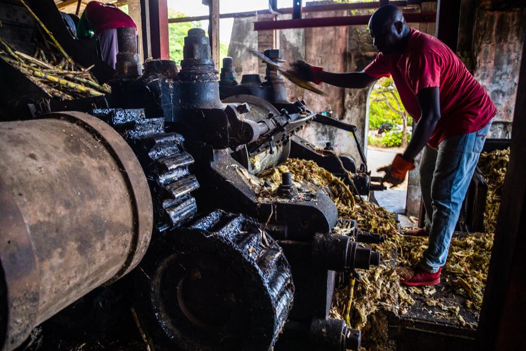 Im laufenden Betrieb werden einzelne Zuckerrohrstücke ein zweites Mal durch die Presse geschickt. Kaum zu glauben, dass diese Maschine schon zu Goethes Zeiten zuverlässig gearbeitet hat / © FrontRowSociety.net, Foto: Georg Berg