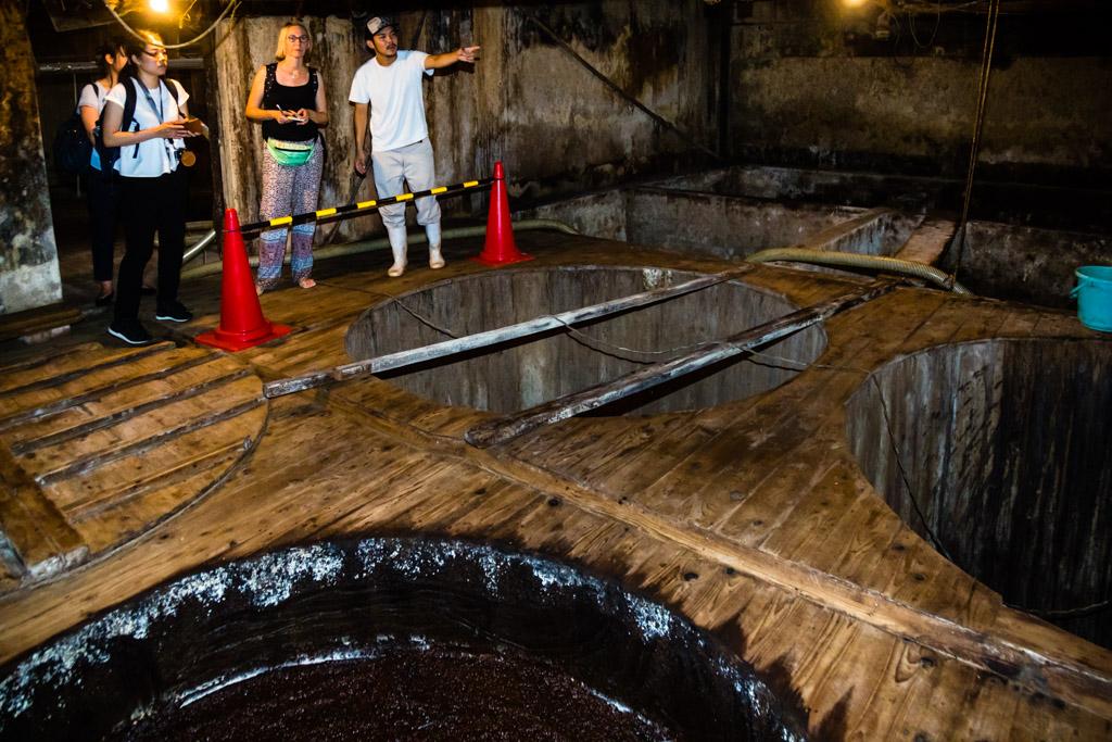 """In riesigen Fässern aus Zedernholz wird Moromi, eine zähflüssige Masse aus gekochten Sojabohnen und geröstetem Weizen zusammen mit Wasser und dem """"tanekoji"""", einem Pilz, der zuvor 3 Tage lang auf den gedämpften Sojabohnen gesprossen ist / © FrontRowSociety.net, Foto: Georg Berg"""