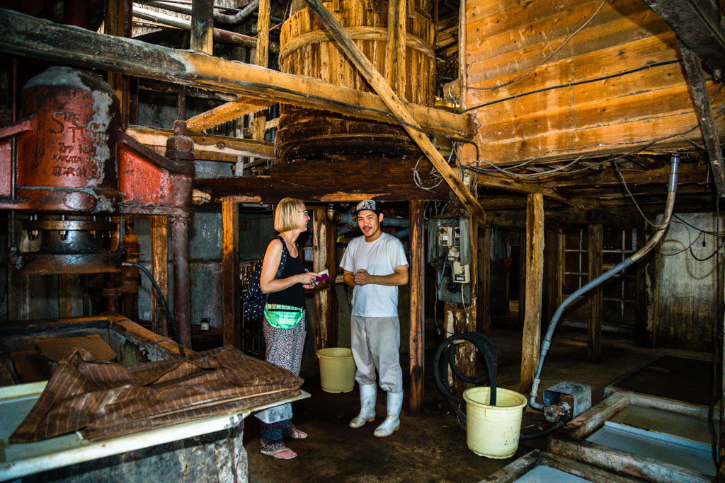Shohei Nozue erklärt Front Row Society Redakteurin Angela Berg, dass das Moromi im Sommer alle sieben Tage und im Winter alle 14 Tage mit einem großen Paddel gerührt wird. Fermentation und Zeit sind die wichtigsten Komponenten für eine hochwertige Sojasauce / © FrontRowSociety.net, Foto: Georg Berg