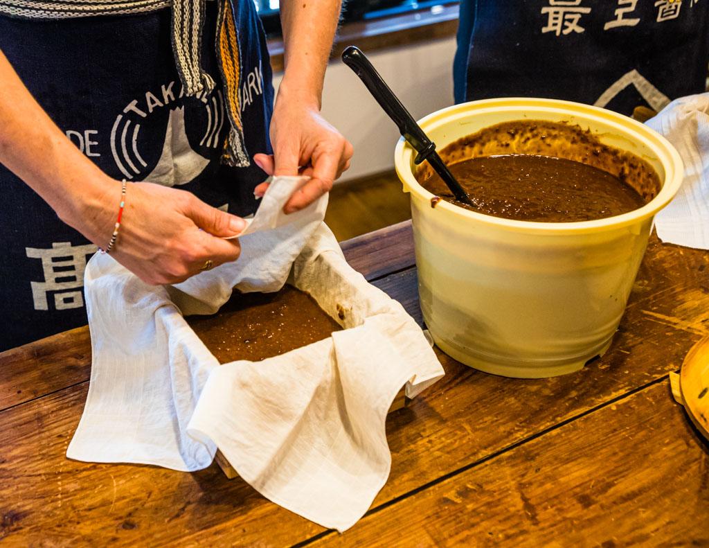 """Nach der Führung durch die Manufaktur geht es im wahrsten Sinne des Wortes ans """"Eingemachte"""". Moromi wird den Workshop-Teilnehmern im kleinen Eimer vorgesetzt. Im Kleinen findet nun statt, was in der Manufaktur mit 1.000 Litern Moromi passiert. Durch die Filterpressung kommen am Ende 800 Liter Sojasauce heraus / © FrontRowSociety.net, Foto: Georg Berg"""