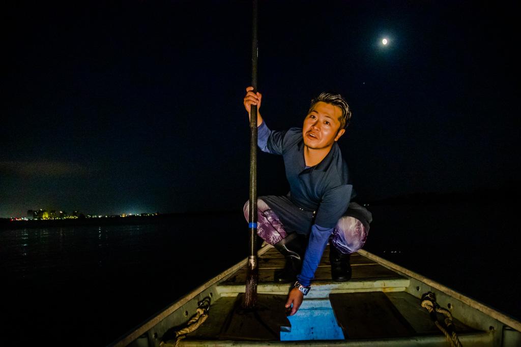 Ikuya Yamamoto öffnet die Luke, in der die Beute gesammelt wird. Der Fang wird mit Hilfe von Aussparungen in den Holzbrettern vom Speer abgestreift und fällt in die Kammer im Bootsrumpf / © FrontRowSociety.net, Foto: Georg Berg