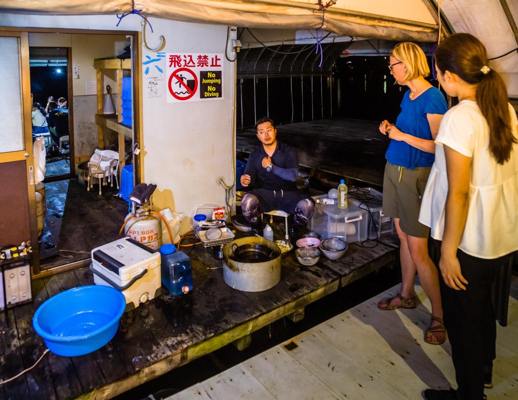 Fischer, Koch und Entertainer. Mit simpelstem Equipment begibt sich Ikuya Yamamoto an die Zubereitung des Fangs. Geschickt werden die Fische geputzt und die Krebse kommen in den Kochtopf. Gäste stellen neugierig Fragen und werden mit einem kühlen Getränk versorgt / © FrontRowSociety.net, Foto: Georg Berg