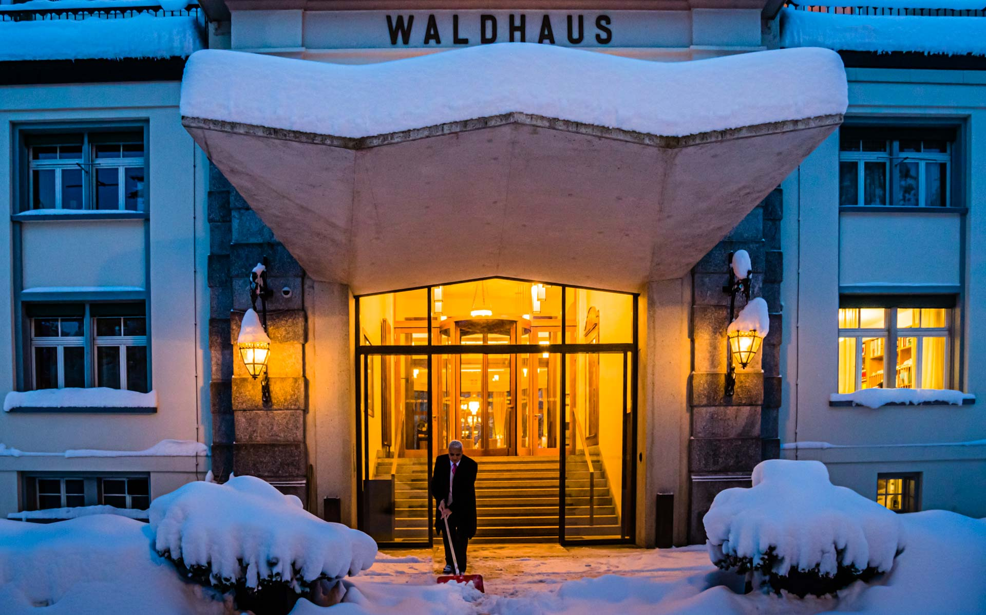 Meterhoher Neuschnee vor dem Waldhaus in Sils wird schon früh morgens weggeräumt. Das Licht in der Lobby leuchtet warm und einladend. Schön zu wissen, dass man sich gleich in einen der Samtsessel im Salon-Bleu fallen lassen kann / © FrontRowSociety.net, Foto: Georg Berg