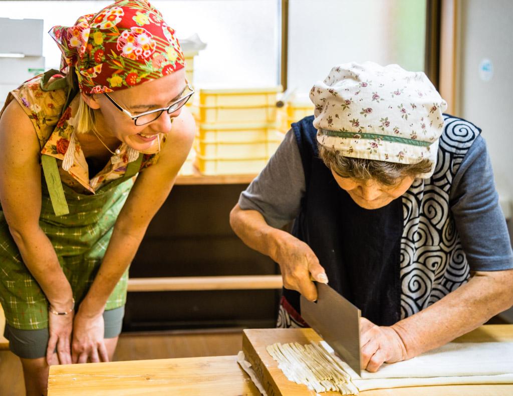 Sumiko Sano zeigt wie dick die Nudeln werden sollen. Was das Foto nicht verrät, ist die Geschwindigkeit, mit der das Messer durch den Teig fährt / © FrontRowSociety.net, Foto: Georg Berg