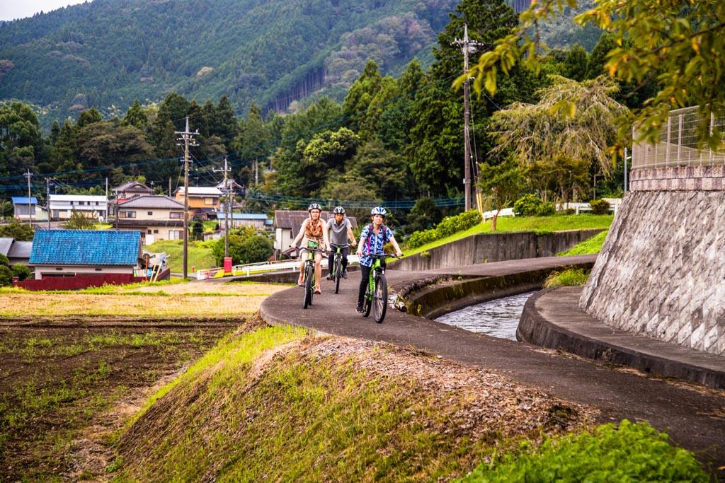 Mit dem Rad unterwegs, vorbei an Bewässerungskanälen für die Felder, auf denen Reis und Buchweizen wächst. Japaner nennen diese Landschaft zwischen Berg und Acker Satoyama / © FrontRowSociety.net, Foto: Georg Berg