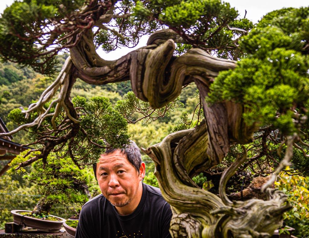 Bonsai-Meister und Garten-Inhaber Toshio Ohsugi im Porträt mit einem 500 Jahre alten Pflegefall. Der Baum wurde den Aufzeichnungen nach um 1920 aus den Bergen von einem Felsen genommen. Seine Wurzeln hatten einen Spalt in den Fels getrieben / © FrontRowSociety.net, Foto: Georg Berg