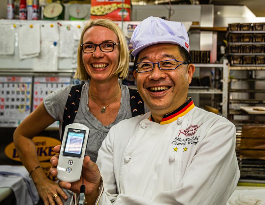 Daiichi Sugiyama trägt eine Bäckerjacke mit schwarz-rot-goldenen Streifen und benutzt virtuos einen mobilen Sprachübersetzer / © FrontRowSociety.net, Foto: Georg Berg
