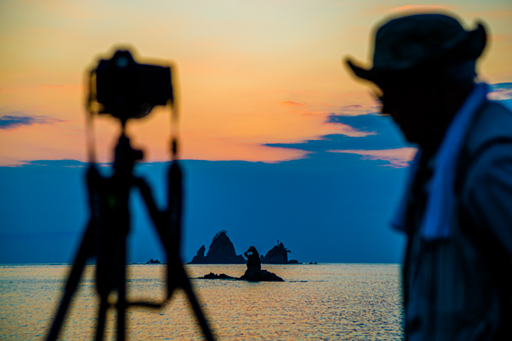 Am Strand der Tago Bay bringen sich abends unzählige Sonnenuntergangs-Fotografen in Stellung und warten auf den Augenblick, in dem sich der Sonnenball für einen kurzen Moment wie ein Edelstein in die natürliche und runde Aussparung der Felsen schiebt / © FrontRowSociety.net, Foto: Georg Berg