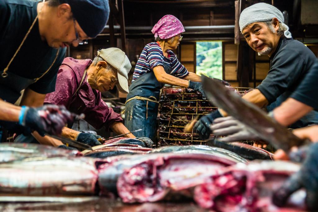 Yasuhisa Serizawa, rechts im Bild. Ihm gegenüber sein Vater, der mit weit über 80 Jahren noch mitzerteilt. Seine Mutter nimmt die Fischhälften und legt sie für den nächsten Arbeitsschritt in einen großen Metallkorb / © FrontRowSociety.net, Foto: Georg Berg