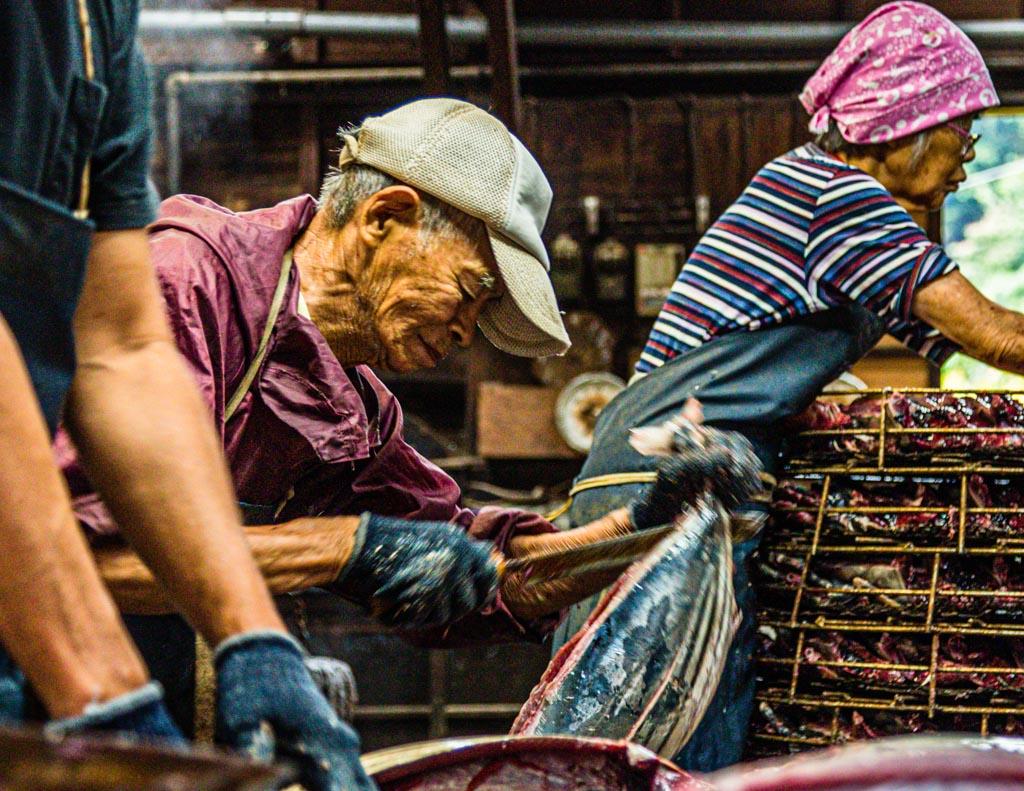 Mit weit über 80 Jahren ist Herr Serizawa noch im Einsatz. Hier beim Zerlegen von Fisch. Namagiri heisst dieser Arbeitsschritt, bei dem die kleine Thunfischart Bonito geteilt und die Innereien entfernt werden / © FrontRowSociety.net, Foto: Georg Berg