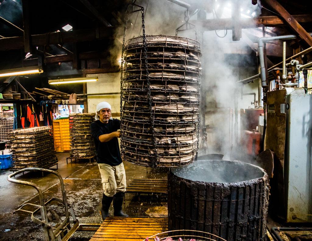 Serizawa führt den Korb, Nikgao genannt, mit den Thunfischhälften in ein maßgeschneidertes Tauchbecken. Dies ist der sensibelste Part in der Herstellung. Denn das vorsichtige Köcheln des Fisches bestimmt seine spätere Form und ist Grundlage für die spätere Geschmacksintensität / © FrontRowSociety.net, Foto: Georg Berg