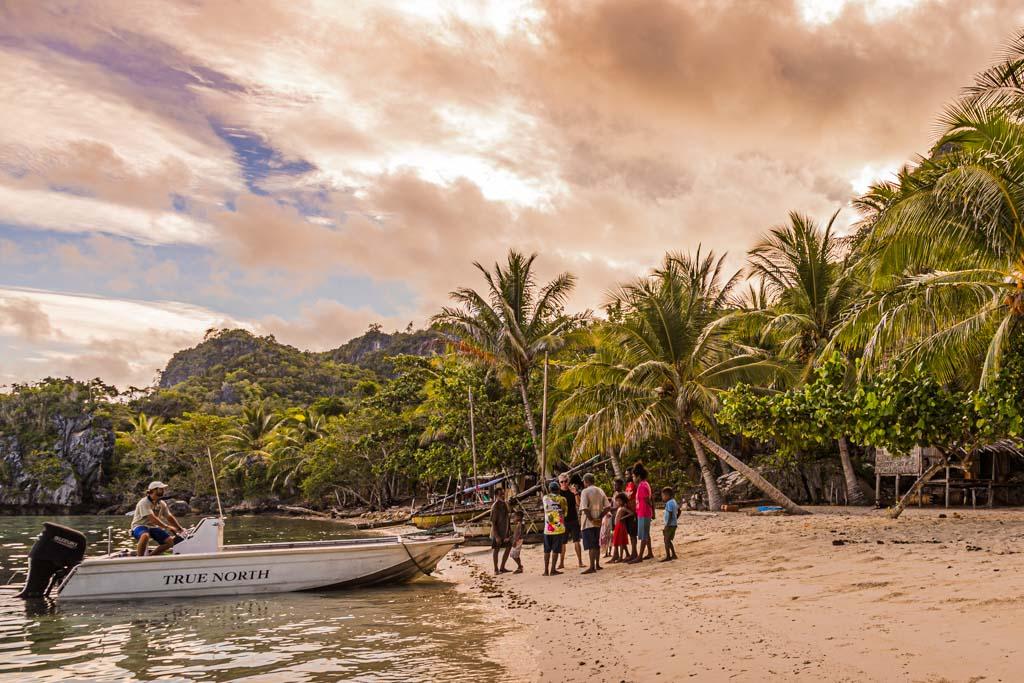 Für die erste Begegnung mit Einheimischen lässt sich nur der mit den Sitten und der Verständigung vertraute Guide Simon Tewson ans Ufer fahren / © FrontRowSociety.net, Foto: Georg Berg