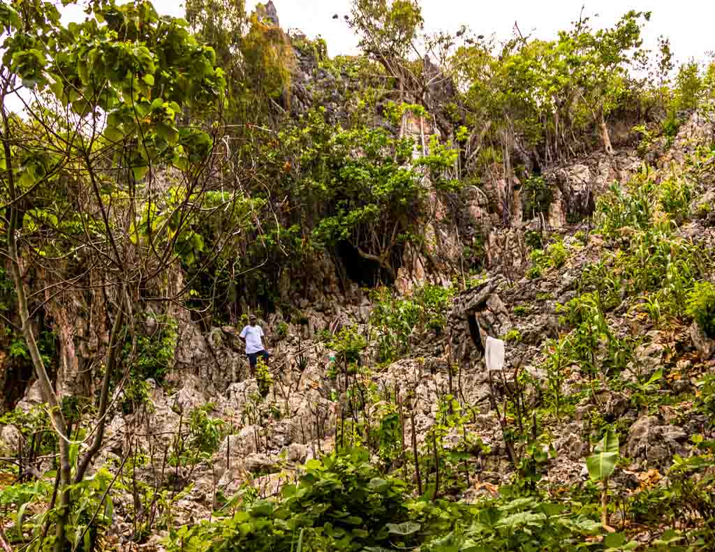 John leads us through stony vegetable fields to an inconspicuous cave / © FrontRowSociety.net, photo: Georg Berg