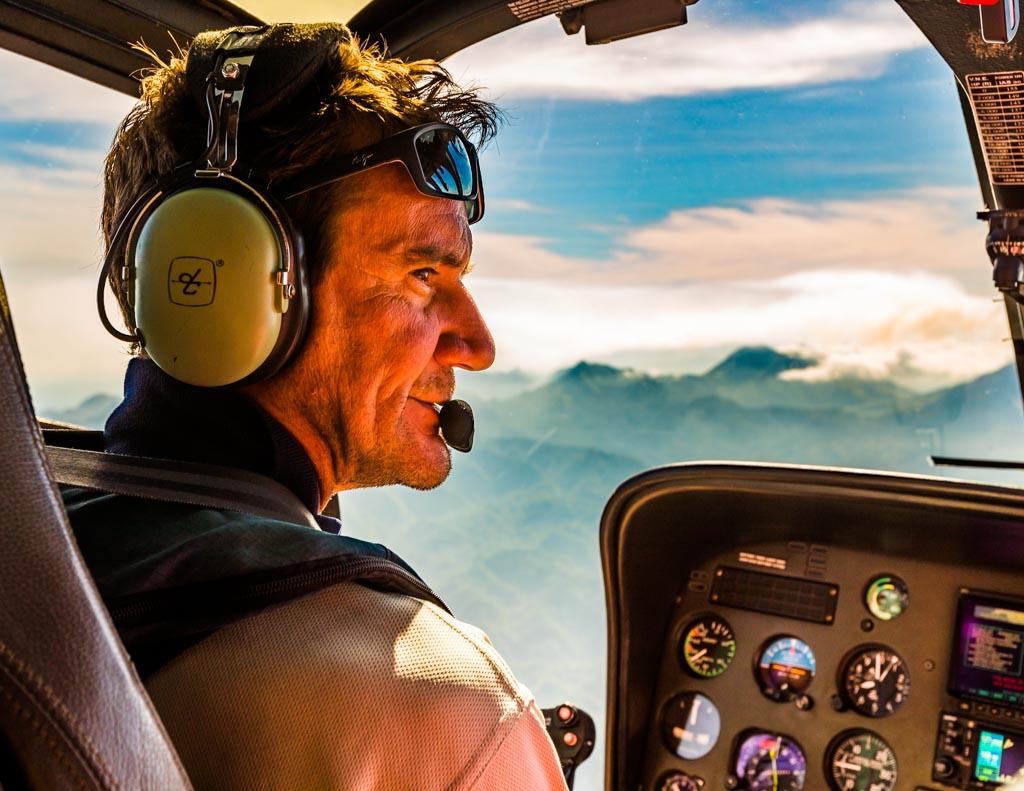 Pilot Alan Carstens erklärt den Mitfliegern alle wichtigen Naturphänomene über die miteinander verbundenen Kopfhörer / © FrontRowSociety.net, Foto: Georg Berg