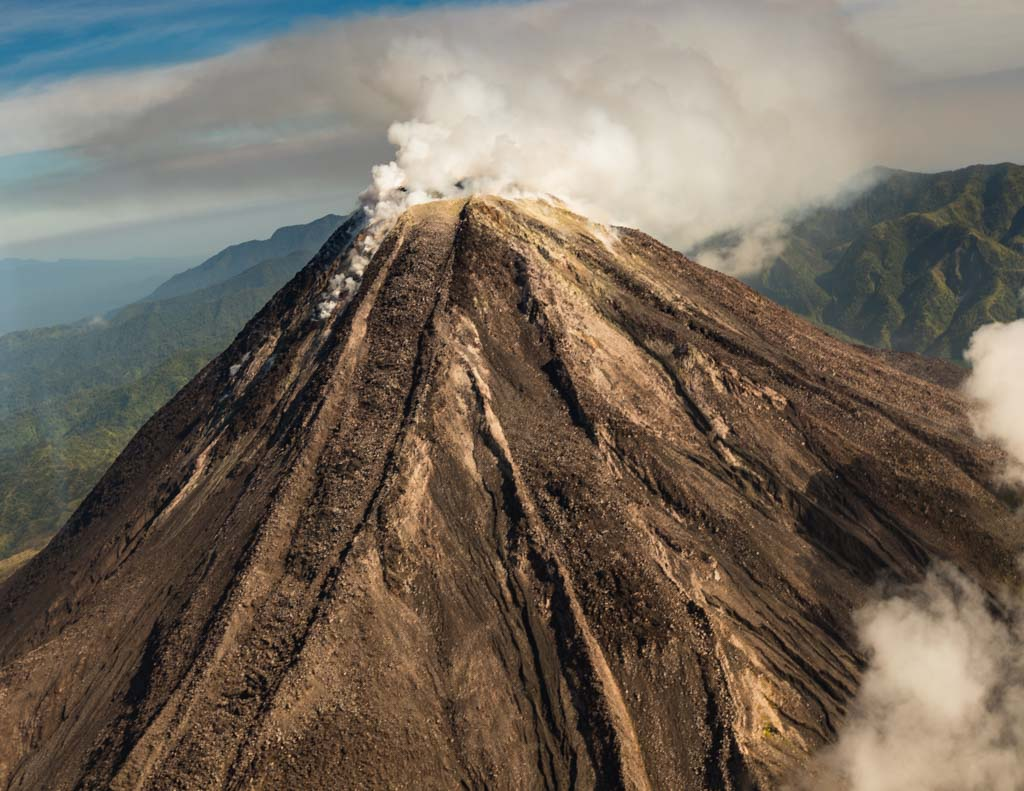 As we approach, the Bagana volcano emits clouds of smoke / © FrontRowSociety.net, photo: Georg Berg