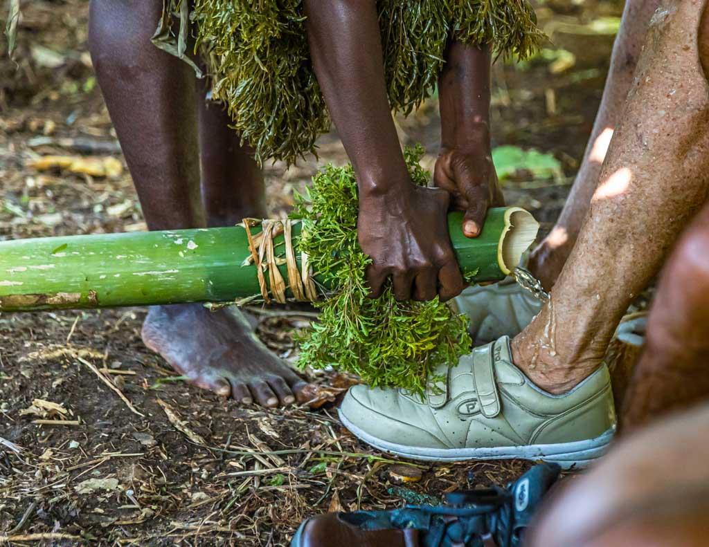 Auf ungewöhnliche Art werden Neuankömmlinge auf Bougainville willkommen geheißen. Mit Wasser aus einem Bambusrohr werden die Füße gewaschen / © FrontRowSociety.net, Foto: Georg Berg